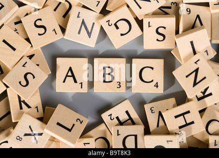 Scrabble pieces with numerous different letters forming ABC - Stock Photo