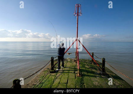 A man casting a fishing line from the end of a jetty on Brighton seafront UK - Stock Photo