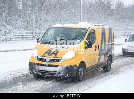 AA automobile association van driving along a snow covered road in winter in england - Stock Photo