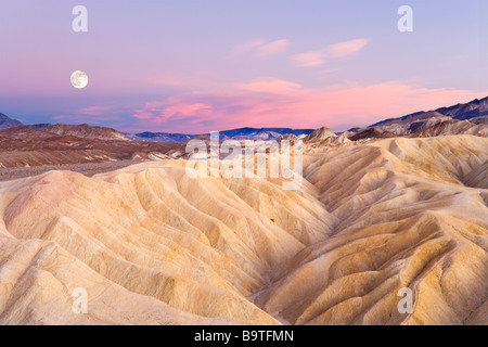 Full moon at sunset looking east at Zabriskie Point, Death Valley National Park, California, USA - Stock Photo