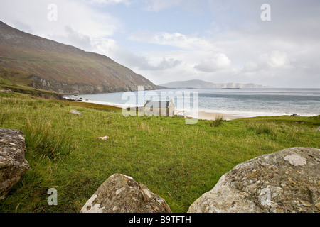 Cottage on Keem Strand. An old parged stone cottage stands  on the shore of Keem Strand or beach at end of the Atlantic - Stock Photo