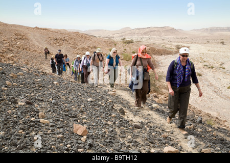 Jordan tourism; Middle aged tourists walking on a guided tour in the desert, Dana, Southern Jordan, Middle East - Stock Photo