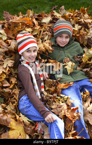 Two children laying in pile of Fall leaves - Stock Photo