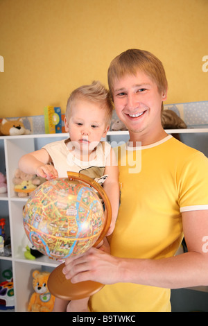 father holds child and globe in hands - Stock Photo
