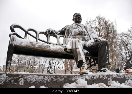 Statue of a man sitting on a bench full of snow, Odessa, Ukraine, Europe - Stock Photo