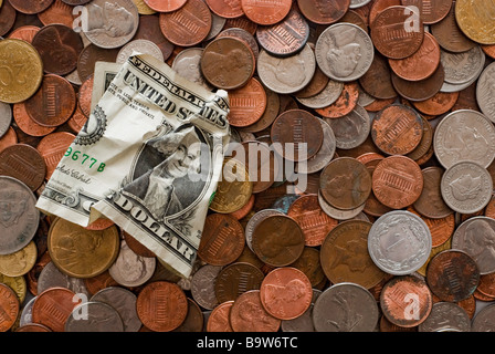 A crumpled dollar bill on top of a layer of coins of multiple currencies - Stock Photo