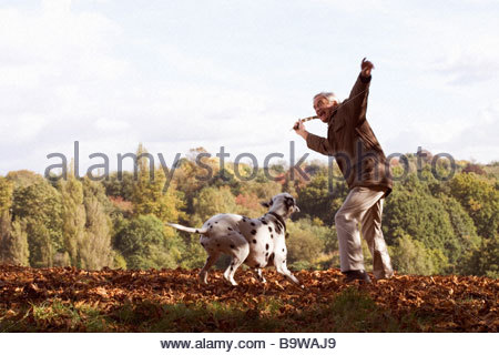 A senior man playing with his dog amongst the autumn leaves - Stock Photo