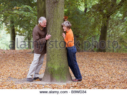 A senior couple peering around a tree, playing hide and seek - Stock Photo