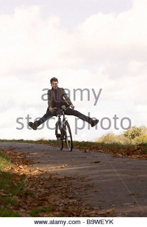 A young woman riding a bicycle, smiling, - Stock Photo