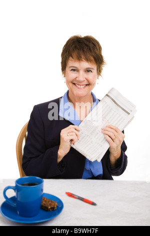 Pretty businesswoman happy about the latest financial news in the paper Isolated on white  - Stock Photo