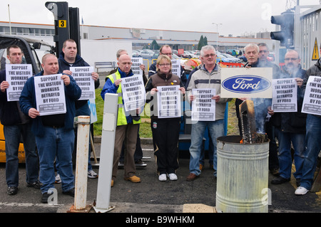 Workers demonstrate against redundancies at a Ford factory by holiding up posters asking for support. - Stock Photo