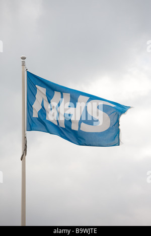 Flag of the National Health Service (NHS) flying outside a UK hospital - Stock Photo