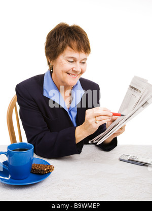 Pretty mature businesswoman looks for a job in the newspaper want ads Isolated on white  - Stock Photo