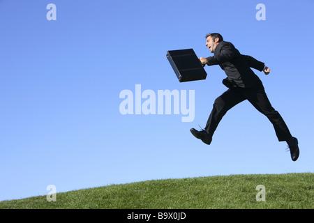 Businessman outdoors jumping - Stock Photo