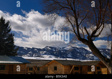 Group of log cabins in Gardiner Montana with Electric Peak in winter - Stock Photo