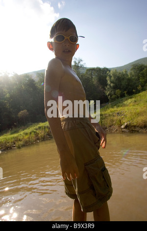 Portrait of 9 year old boy at swimming pond - Stock Photo