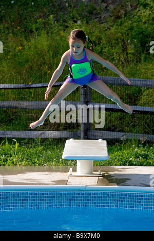 5 Year Old Girl Jumping Off Diving Board Into Swimming Pool Stock Photo Royalty Free Image
