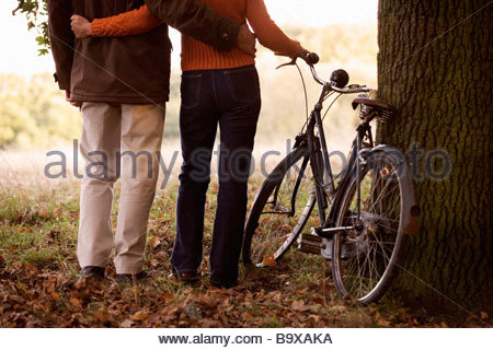 A senior couple standing next to a bicycle, with arms around each other - Stock Photo