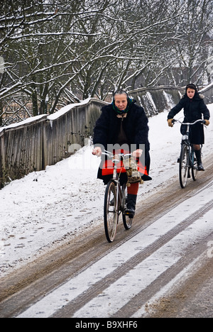 Two women dressed with traditional costumes riding bicycles on a snowed road, Maramures, Romania, Europe - Stock Photo