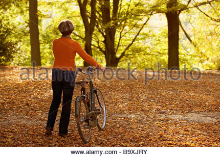 A senior woman pushing a bicycle in autumn time - Stock Photo