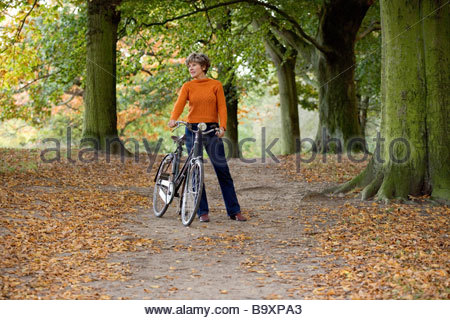A senior woman standing with a bicycle in autumn time - Stock Photo