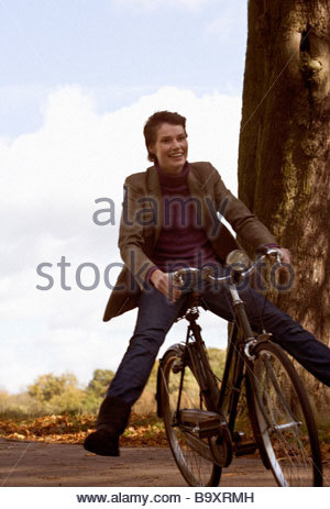 A young woman riding a bicycle downhill - Stock Photo