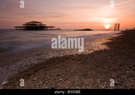 Sunset at Brighton, East Sussex, looking towards the burnt out remains of West Pier. - Stock Photo