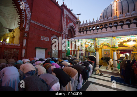 Praying at Hazrat Nizamuddin Dargah Muslim Shrine in Old Delhi India - Stock Photo