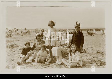 1920's postcard of family on beach, pastimes, U.K. - Stock Photo