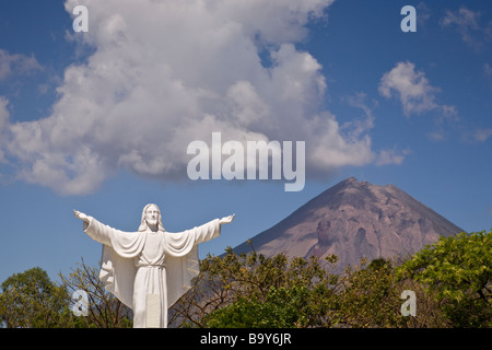 Statue of Jesus at the Cementerio Los Angeles in Moyogalpa, Nicaragua on Ometepe Island with the Volcan Concepcion - Stock Photo