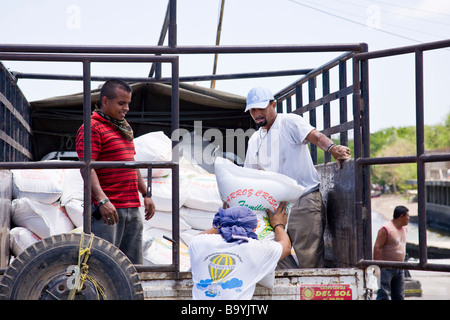 Workers loading supplies from the mainland onto a truck on the dock in Moyogalpa, Ometepe Island, Nicaragua. - Stock Photo