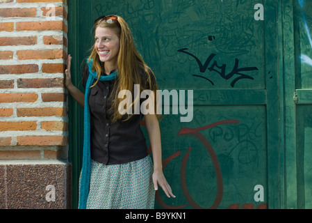 Young woman standing in alley, looking away, smiling - Stock Photo
