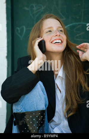Young woman talking on cell phone, playing with hair - Stock Photo