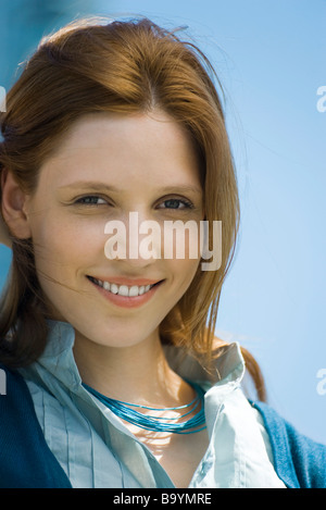 Red haired woman smiling at camera, portrait - Stock Photo