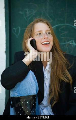 Young woman with strawberry blonde hair and freckles talking on cell phone, smiling - Stock Photo