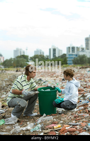Young male and boy picking up recyclable materials in garbage heap - Stock Photo
