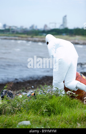 Person in protective suit cleaning up polluted shore - Stock Photo