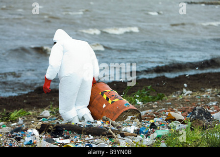 Person in protective suit carrying barrel of hazardous waste on polluted shore - Stock Photo
