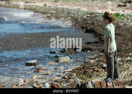 Boy standing on shore, looking out at polluted water - Stock Photo