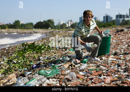 Male picking up trash on polluted shore - Stock Photo