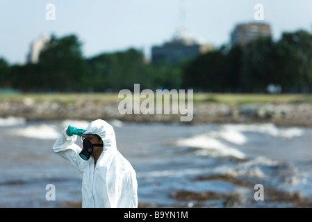 Person in protective suit looking at polluted water, side view - Stock Photo