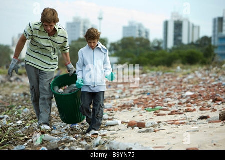 Young male and boy collecting recyclable materials in garbage dump - Stock Photo