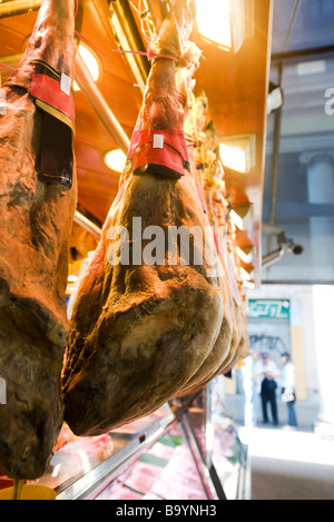 Smoked pork legs hanging on display in butcher's shop - Stock Photo