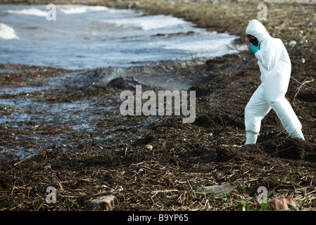Person in protective suit walking along polluted shore - Stock Photo
