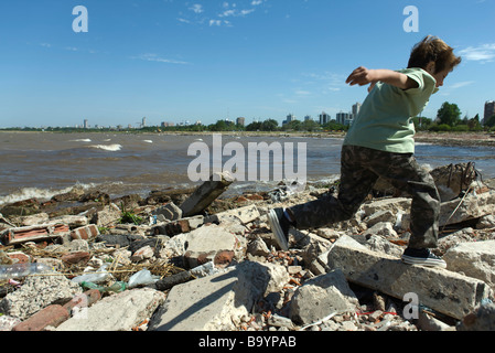 Boy running on shore littered with debris, city in background - Stock Photo