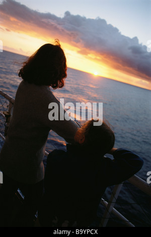 Mother and daughter on deck, looking at sunset - Stock Photo