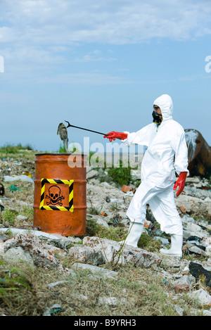 Person in protective suit placing dead fish in hazardous waste barrel - Stock Photo