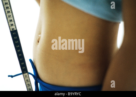 Woman's midriff and measuring tape - Stock Photo