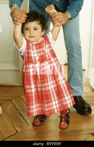 Mother helping daughter walk - Stock Photo