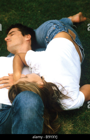 Couple lying on ground together, woman's head resting on man's stomach - Stock Photo